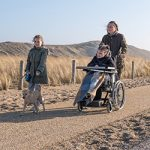 A family, including a daughter in a wheelchair, walking along the beach emphasising the work of the Court of Protection