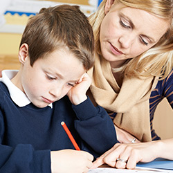 Education following a brain injury. A teacher helping a child with his work.
