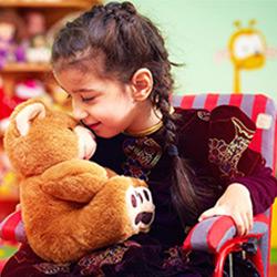 A girl in a wheelchair lovingly cuddles her teddy bear