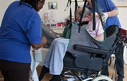 A brain injured man who has his care funded, is helped into a wheelchair by two carers
