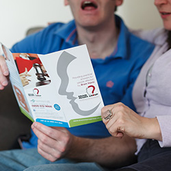 A man with a brain injury looks at a Brain Injury Group brochure on brain injury compensation claims with his carer