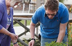 A man with a brain injury and his carer enjoy gardening