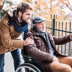 An elderly man in a wheelchair with his son acting as carer
