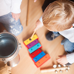 A child with an acquired brain injury playing with a colourful xylophone and surrounded by other musical instruments as part of a music therapy session
