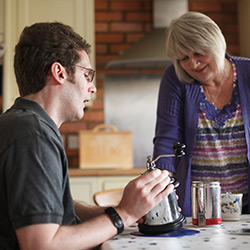 Mental Capacity Act - a brain injured man is supported by his carer as he grinds coffee beans
