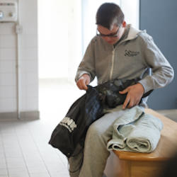A brain injured boy alone in a dressing room packs his swimming gear into a bag.