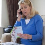 A Lady reading a Brain Injury Group brochure highlighting the important step of researching financial matters