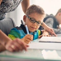 a boy with special educational needs works in a classroom