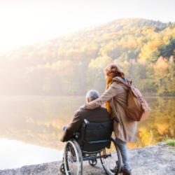 A brain injured man in a wheelchair and his partner thoughtfully look out across a forest lake as if they were thinking of Statutory wills and gifts