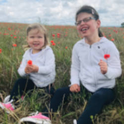 Ella (the subject of our story) and her sister Poppy playing in a field of flowers