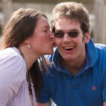 A smiling man with a brain injury is kissed by his wife, illustrating post traumatic growth amongst people with a brain injury and our Post traumatic growth webinar