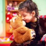 A young child cuddles a teddy bear illustrating our Continuing care for children and young persons living with brain injury webinar