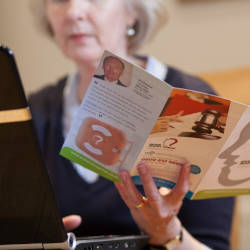 A lady sits at a laptop computer reading a Brain Injury Group leaflet illustrating our interim payments webinar