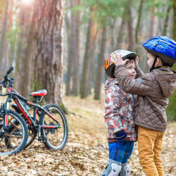 Two children with cycle helmets adjust each other's helmet as their bikes sit nearby illustrating the importance of cycle helmets preventing serious brain injury.