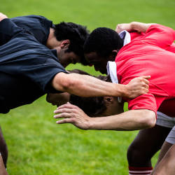 An image of rugby players locking heads about to engage in a scrum illustrating the head impacts and brain injuries in sport