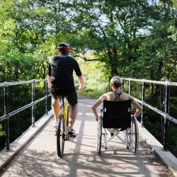 A cyclist and wheelchair user cross a forest bridge illustrating our Court of Protection Costs Masterclass webinar