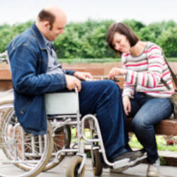 A man in a wheelchair plays chess with his carer illustrating our Managing ongoing welfare decisions webinar