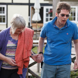 A man with a brain injury is supported by a family member illustrating gratuitous care claims where a family member cares for a brain injured person within their family