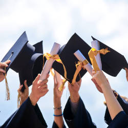 Graduation hats thrown into the air celebrating graduation from University illustrating how people with a brain injury can get funded support at University
