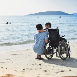 A man on the beach next to his son in a wheelchair illustrating this article explaining personal injury trusts