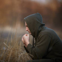 A brain injured man sits alone deep in thought in a field illustrating our brain injury and men's mental health webinar
